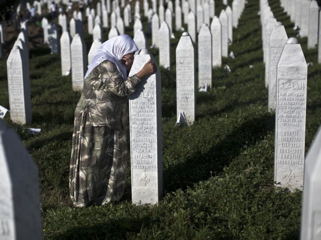A woman weeps as she visits the grave of a family member at the Potocari memorial complex near Srebrenica, 150 kilometers (94 miles) northeast of Sarajevo, Bosnia and Herzegovina, Saturday, July 11, 2015. Twenty years ago, on July 11, 1995, Serb troops overran the eastern Bosnian Muslim enclave of Srebrenica and executed some 8,000 Muslim men and boys, which International courts have labeled as an act of genocide, and newly identified victims of the genocide are still being re-interred at Srebrenica. (AP Photo/Marko Drobnjakovic)